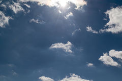 Blue sky with white Cumulus clouds. At the top the sun shines. royalty free stock image