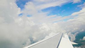 Blue sky and white heap clouds looking through porthole of flying airplane 4k. Blue sky and white heap clouds looking through porthole of flying airplane. UHD stock video footage