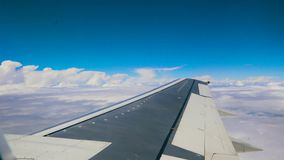Blue sky and white heap clouds looking through porthole of flying airplane 4k. Blue sky and white heap clouds looking through porthole of flying airplane. UHD stock footage