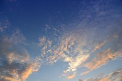 Blue sky with white and orange clouds. Blue sky with white and orange clouds in evening before sunset Stock Photos