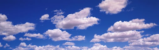 Blue sky with white puffy clouds Royalty Free Stock Image