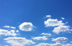 Blue sky and white puffy clouds stock image