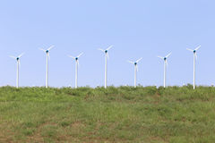Blue sky and wind turbine on green lawn in the summer. Stock Photo