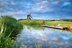 Blue sky and windmill reflected in river Stock Images