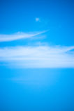 Blue sky & wispy cloud Stock Images