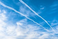 Jet Aircraft Contrails, Clouds, and Blue Sky. Blue sky, wispy white clouds, and contrails from high flying aircraft stock photo