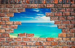 Free Blue Sky With Sea Through The Hole In The Brick Wall Stock Image - 74930021