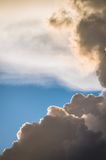 Blue sky with yellow backlit clouds coming from the sun that is shining through with light . Royalty Free Stock Images