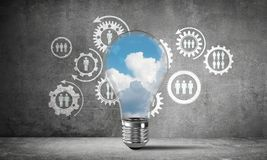 Blue skyscape and clouds inside lightbulb. Lightbulb with cloudly skyscape inside placed against sketched social gear structure on wall. 3D rendering Stock Images