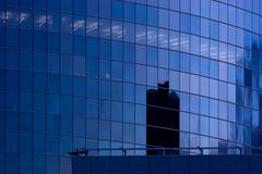 Blue skyscraper building windows. Blue corporate office building facade and reflection of other skyscraper in late evening Royalty Free Stock Image
