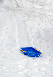 Blue sled on an icy snow hill Stock Images