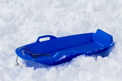 Blue sled in the snow. Plastic blue sled for skiing on snow Royalty Free Stock Photos