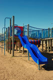 Blue Slide Play Structure. Childhood play structure with clear blue sky and sand royalty free stock image