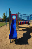 Blue Slide on Play Structure. Childhood play structure with blue slide, clear blue sky and sand Stock Photos