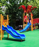 Blue Slides with Green Elastic Rubber Floor for Children, Playground. Blue Slides with Green Elastic Rubber Floor for Children in the Park Stock Photos