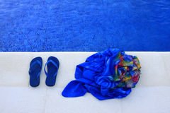 Blue slippers. Slippers standing on edge of a pool Royalty Free Stock Image