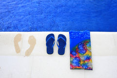 Blue slippers and footprints. On edge of a pool Stock Photography