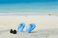 Blue slippers and sunglass on the beach. Blue slippers and sunglass on the white beach Royalty Free Stock Photos