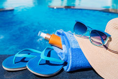 Blue slippers with sunscreen cream, towel, straw hat and sunglas Stock Photography