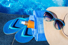 Blue slippers with sunscreen cream, towel, straw hat and sunglas Stock Photo