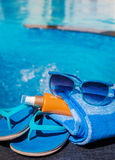 Blue slippers, sunsscreen cream and sun glasses near swimming po Stock Images