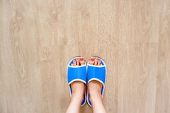 Blue Slippers on Women is Legs and Feet Over Wood at Bedroom. Woman in Sandals, Clear Warm Shoes Accessory. Soft Comfortable Home royalty free stock photos
