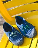 The blue slippers on a yellow chair Stock Photography