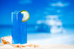 Blue slush ice drink in glass with seascape. Blue slush ice drink in glass on sea beach background Stock Photo