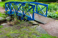 Blue small bridge over river stream creek in garden. Nature. Royalty Free Stock Photography
