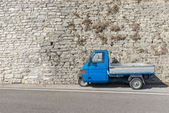 Blue small italian transport vehicle. In front of a bright stone wall royalty free stock images