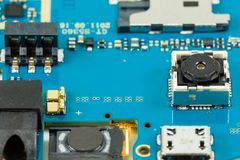 Blue smartphone circuit board showing integrated camera. And electronic elements stock image