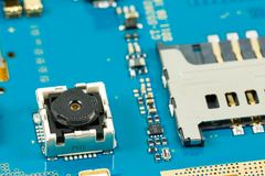 Blue smartphone circuit board showing integrated camera. And electronic elements stock photo