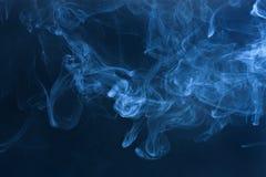 Blue smoke. Dense blue smoke on a black background Stock Photo