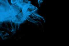 Blue smoke on black. Blue smoke swirling against a black background Royalty Free Stock Photography
