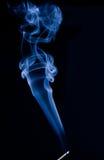 Blue Smoke on Black. Blue smoke drifting lazily upward from a smoldering incense stick, on black background Stock Photo