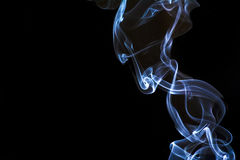 Blue smoke from a candle during nighttime. Royalty Free Stock Image