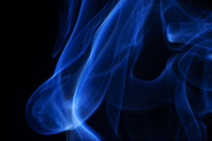 Blue smoke over black background. Stock Photo