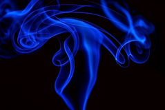 Blue smoke over black background. Abstract blue smoke over a black background Royalty Free Stock Image