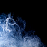 Blue smoke swirls over black Royalty Free Stock Images