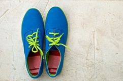 Blue sneaker on cement floor. Pair of blue with green rope sneaker on textured cement floor Royalty Free Stock Photos