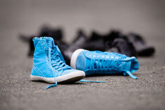 Blue Sneakers. Lying on asphalt with elegant classic shoes in background Stock Images