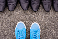 Blue Sneakers. Lying on asphalt against elegant classic shoes royalty free stock photo