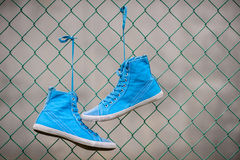 Blue Sneakers. Hanged on fence stock images