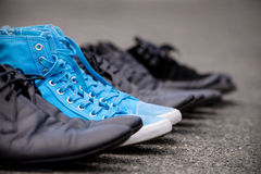 Blue Sneakers. Lying on asphalt with elegant classic shoes royalty free stock image