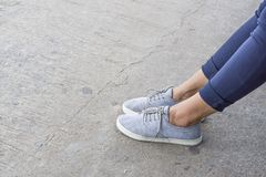 Blue sneakers on asian female feet. With copy space for text. fashion concept. waiting concept Royalty Free Stock Image