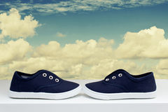 Blue sneakers on background cloudy sky. Sports theme Royalty Free Stock Photos