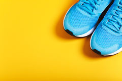 Blue sneakers on black background. Blue sneakers on yellow background. Concept of healthy life, everyday training and force of will Stock Images