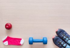 Blue sneakers, blue dumbbell, red Apple, pink socks, sport flat Royalty Free Stock Photography