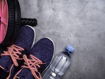 Blue sneakers with coral color shoelacer, bottle of water, sport wheel on stone background. Concept of healthy lifestile, everyday. Blue sneakers and bottle of stock photos