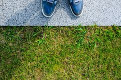 Blue Sneakers on Granite Pavement Near Grass Lawn. Top View Royalty Free Stock Photography